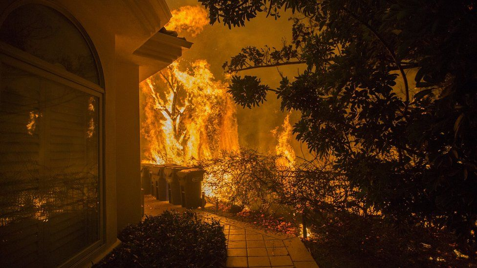 Flames approach a house during the Woolsey Fire on November 9, 2018 in Malibu, California