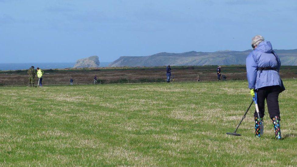 Metal detectorists in a field