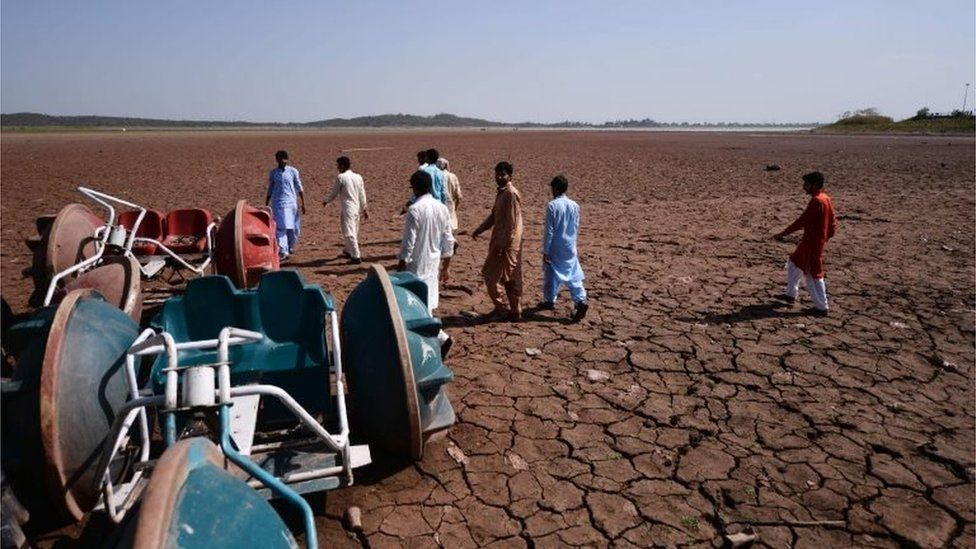 In this picture taken on June 19, 2018, Pakistani residents walk over a dried portion of the Rawal dam in Islamabad.
