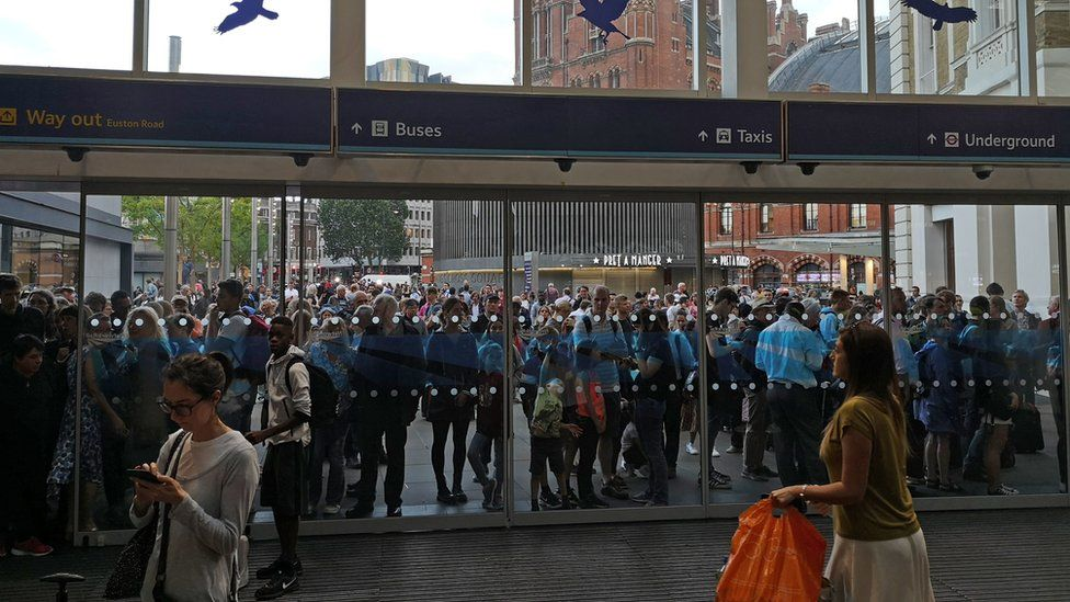 People waiting outside of King's Cross station, London, as all services in and out of the station have been suspended