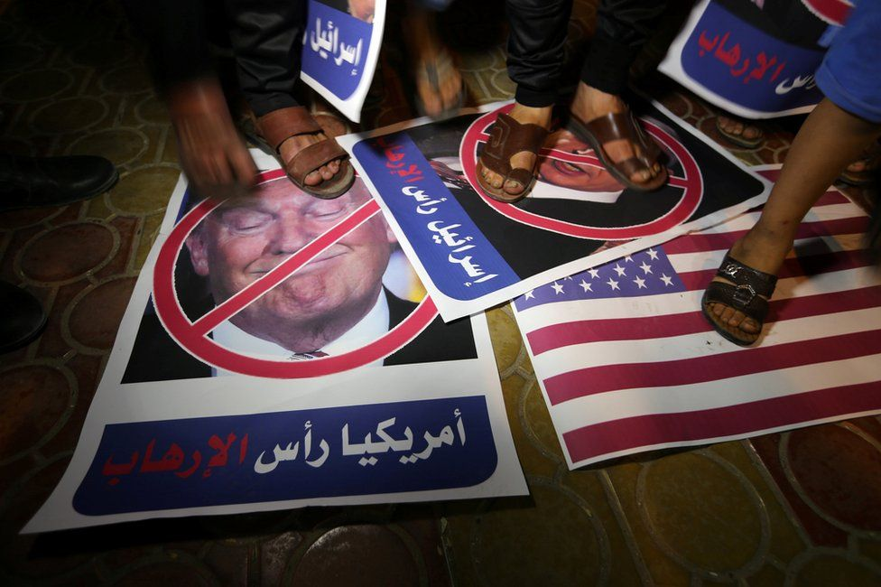 A Palestinian demonstrator steps on a poster depicting Donald Trump in Rafah, in the southern Gaza Strip, 22 May