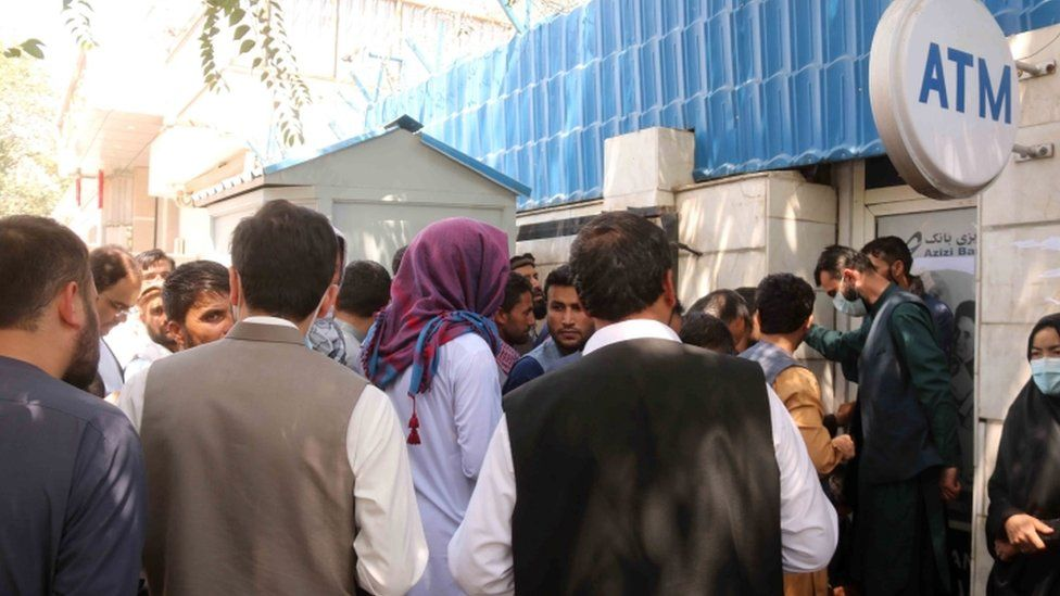 Afghans gather outside a closed bank in Kabul, Afghanistan, 25 August 2021