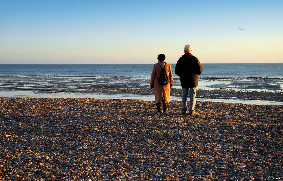 Two elderly people walk on a beach
