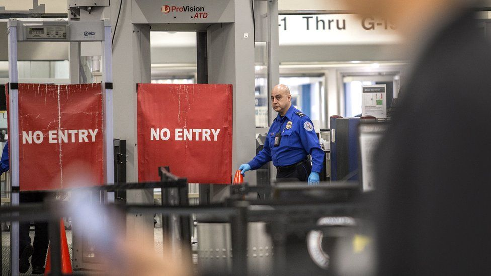 A TSA officer closes the entrance of the Miami International Airport's Terminal G, during the government shutdown, in Miami, Florida, 12 January 2019