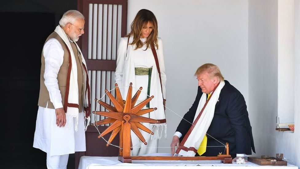 US President Donald Trump (R) and First Lady Melania Trump (C) are accompanied by India's Prime Minister Narendra Modi as they visit the Gandhi Ashram in Ahmedabad on February 24, 2020.