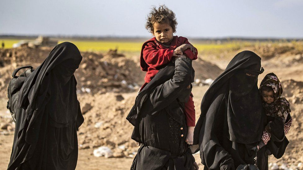 Fully-veiled women carry their children after being evacuated from the last IS-held territory in the eastern Syrian village of Baghuz (6 March 2018)