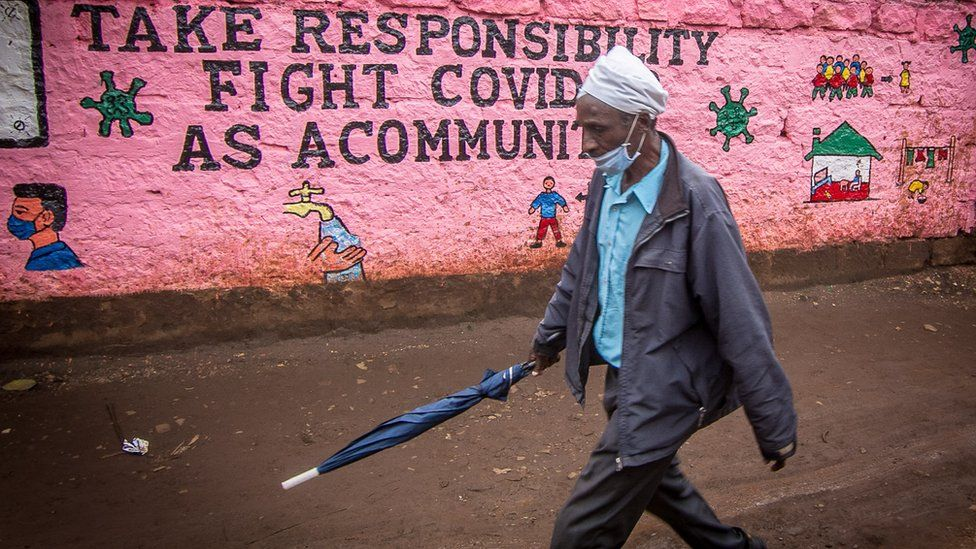 A man wearing a face mask as a precaution, walks past a wall with an awareness graffiti during the corona virus pandemic