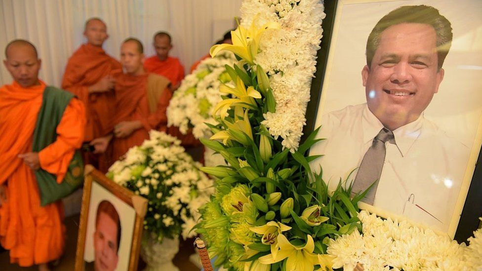 Cambodian Buddhist monks walk past portraits of Kem Ley, a political analyst and pro-democracy campaigner, during a funeral ceremony in Phnom Penh