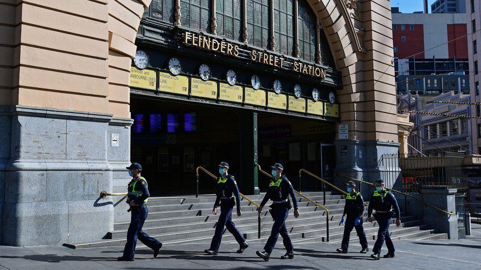 Police patrol outside Flinders Street Station during Melbourne's virus lockdown