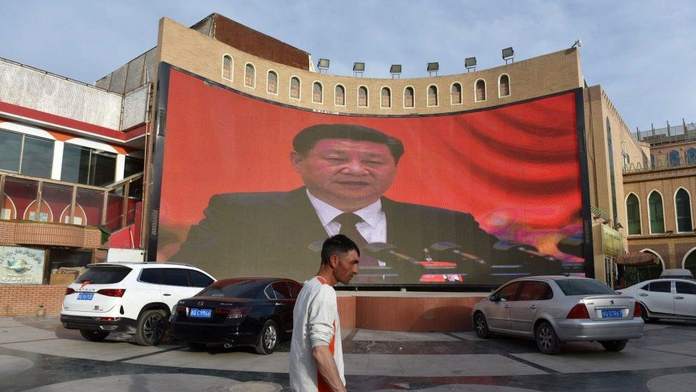 A man walking past a screen showing images of China's President Xi Jinping in Kashgar in China's northwest Xinjiang region