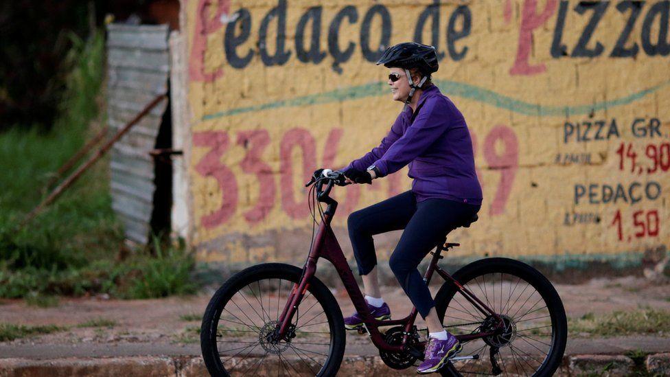 President Dilma Rousseff rides her bicycle near the Alvorada Palace in Brasilia, 15 April 2016.