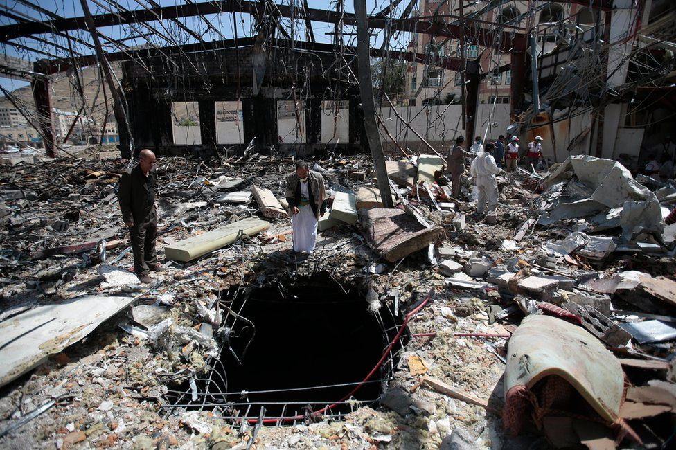 People inspect a funeral hall destroyed in a coalition air strike in Sanaa on 8 October
