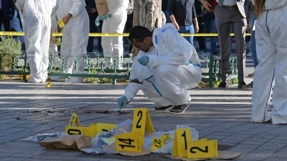 Tunisian forensics experts inspect the site of a suicide attack in the Tunisian capital Tunis