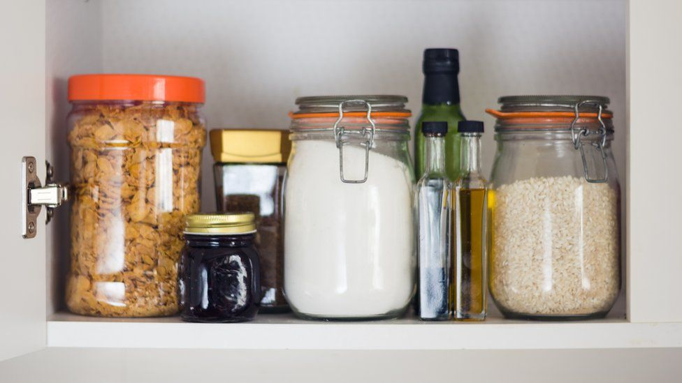 Image shows food including jam, cereal and rice in a cupboard