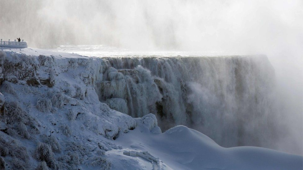 A person takes a selfie beside on the US side of Niagara Falls as seen from Niagara Falls, Ontario, Canada on January 31, 2019
