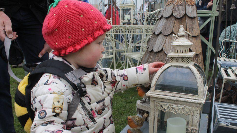Cerys o Dreganna yn cael golwg agos ar rai co'r neyddau sydd ar werth // 17-month-old Cerys from Canton taking a close look at some of the objects on display