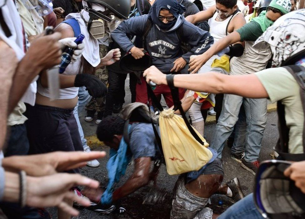 Opposition demonstrators pour petrol over an alleged thief during a protest against the government of President Nicolas Maduro in Caracas on May 20, 2017
