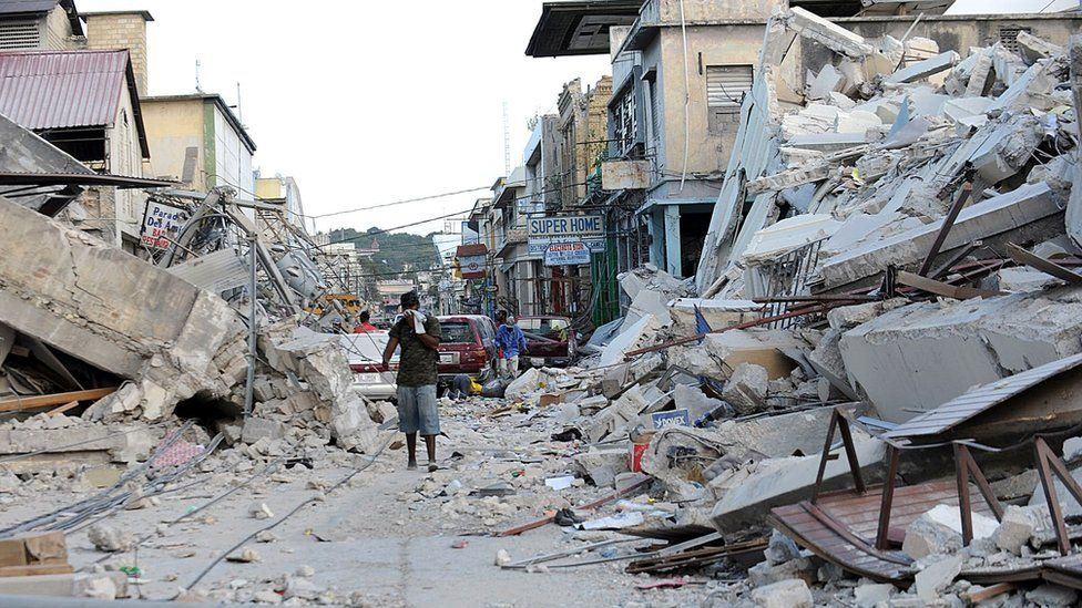 a man covers his face as he walks amid the rubble of a destroyed building in Port-au-Prince on 14 January, 2010