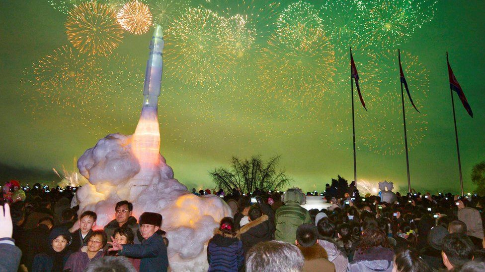 Visitors pose for a photo in front of an ice sculpture of an intercontinental ballistic missile at the Pyongyang Ice Sculpture Festival in Pyongyang, 31 Dec 2017