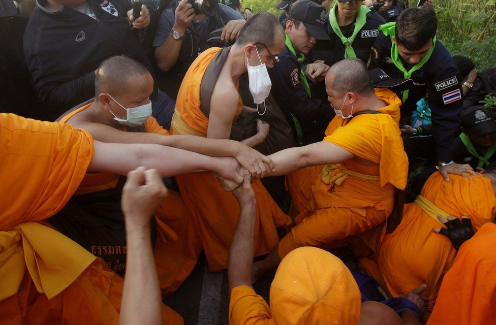 Buddhist monks of the Dhammakaya sect temple pull their felllow monk as they scuffle with Thai policemen outside the temple in Pathum Thani, north of Bangkok, Thailand, Monday, 20 February 2017.