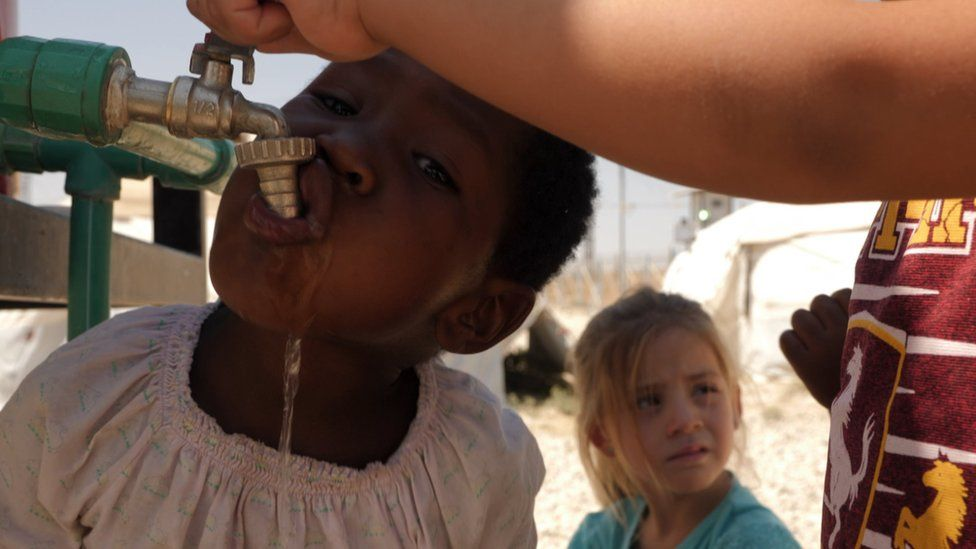 Child drinking from a water tap