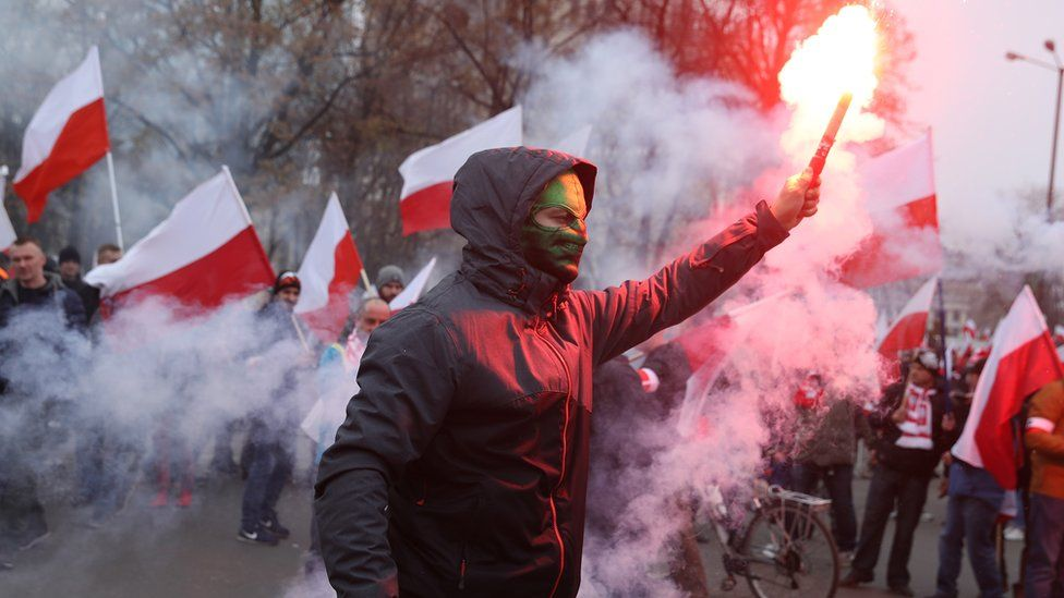 A masked participant holds up a flare prior to the planned March of Independence to mark the 100th anniversary of the reinstatement of Polish independence in Warsaw, 11 November 2018
