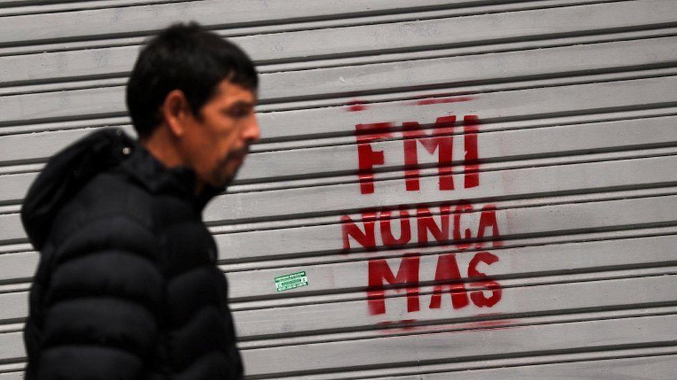 "Man walks past graffiti reading ""IMF never again"" in Buenos Aires, 1 June 2018"