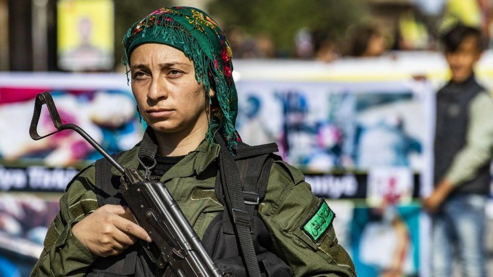 A member of the Kurdish Internal Security Force stands guard during a protest against the Turkish assault on north-eastern Syria