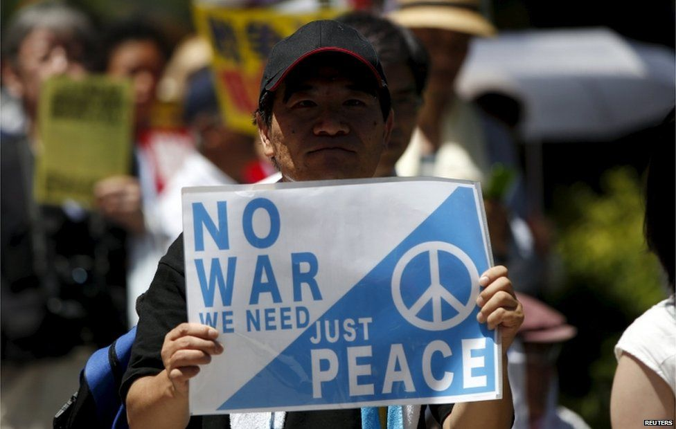 """A protester holds a placard during a rally against Japan's Prime Minister Shinzo Abe""""s administration and his security-related legislation in front of the parliament building in Tokyo 15 July, 2015."""