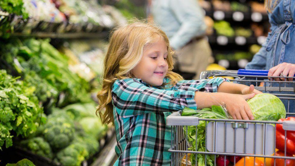child in the veg aisle