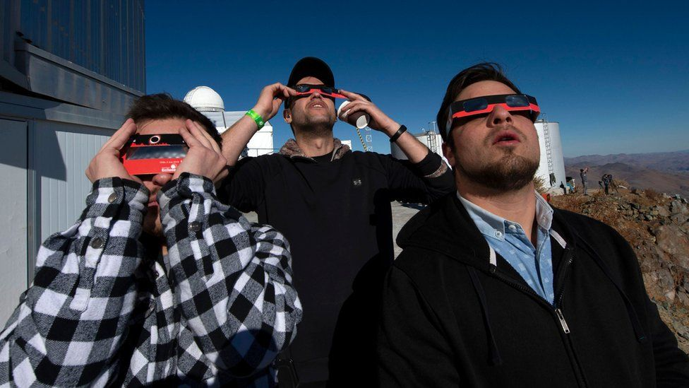 People watch a solar eclipse at La Silla European Southern Observatory (ESO) in La Higuera, Coquimbo Region, Chile