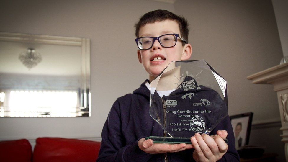 Harley holding a trophy he was given for the work he does to support his mother