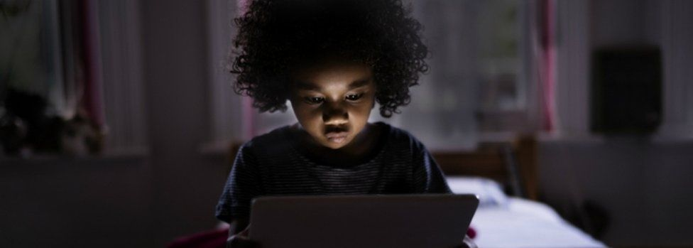 Child surfing internet on a computer tablet in his bedroom