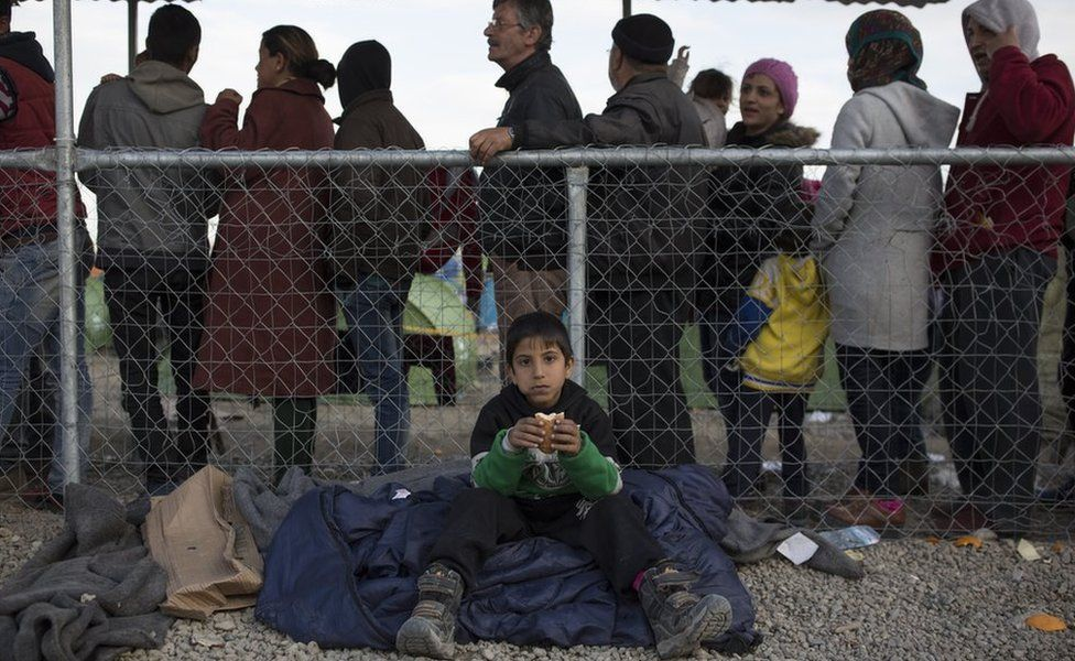 Boy eats a sandwich as people queue for registration documents at the Greek-Macedonia border