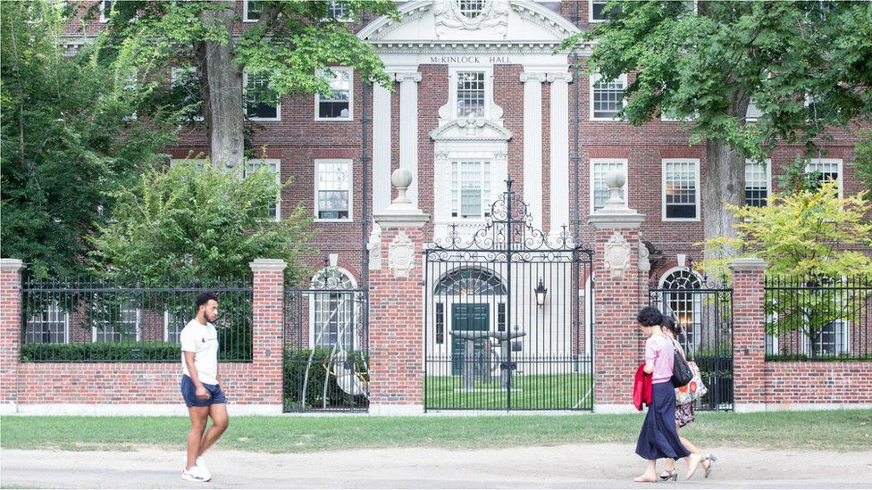 Pedestrians walk past a Harvard University building in August 2018.