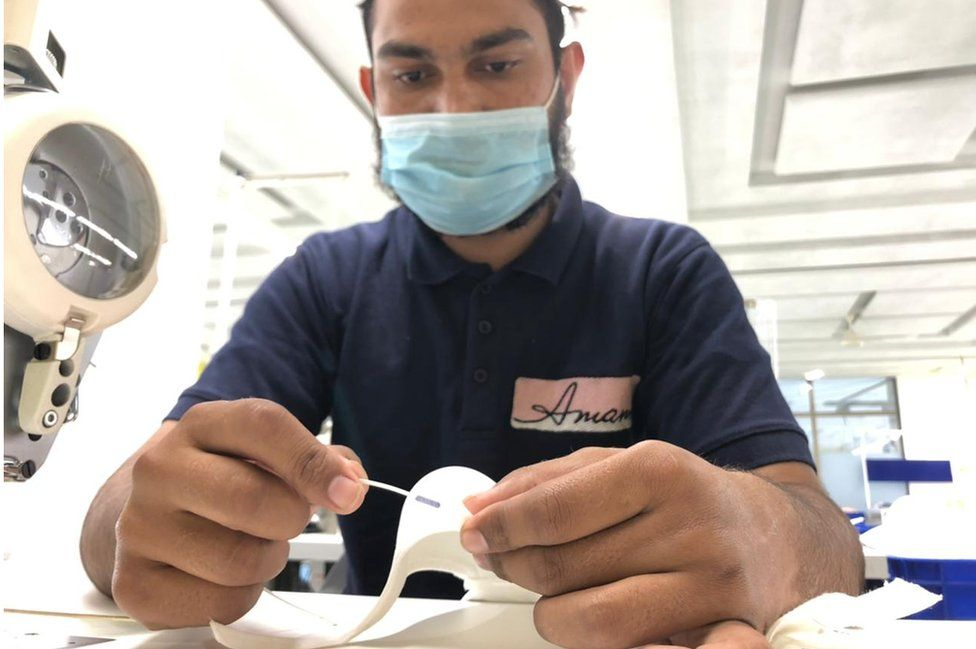 Anwar adds stitching to a bra
