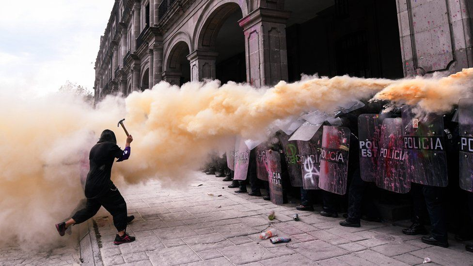 A woman confronts a riot police line during a protest against gender-based violence on International Women's Day, 8 March 2021, in Toluca, Mexico.