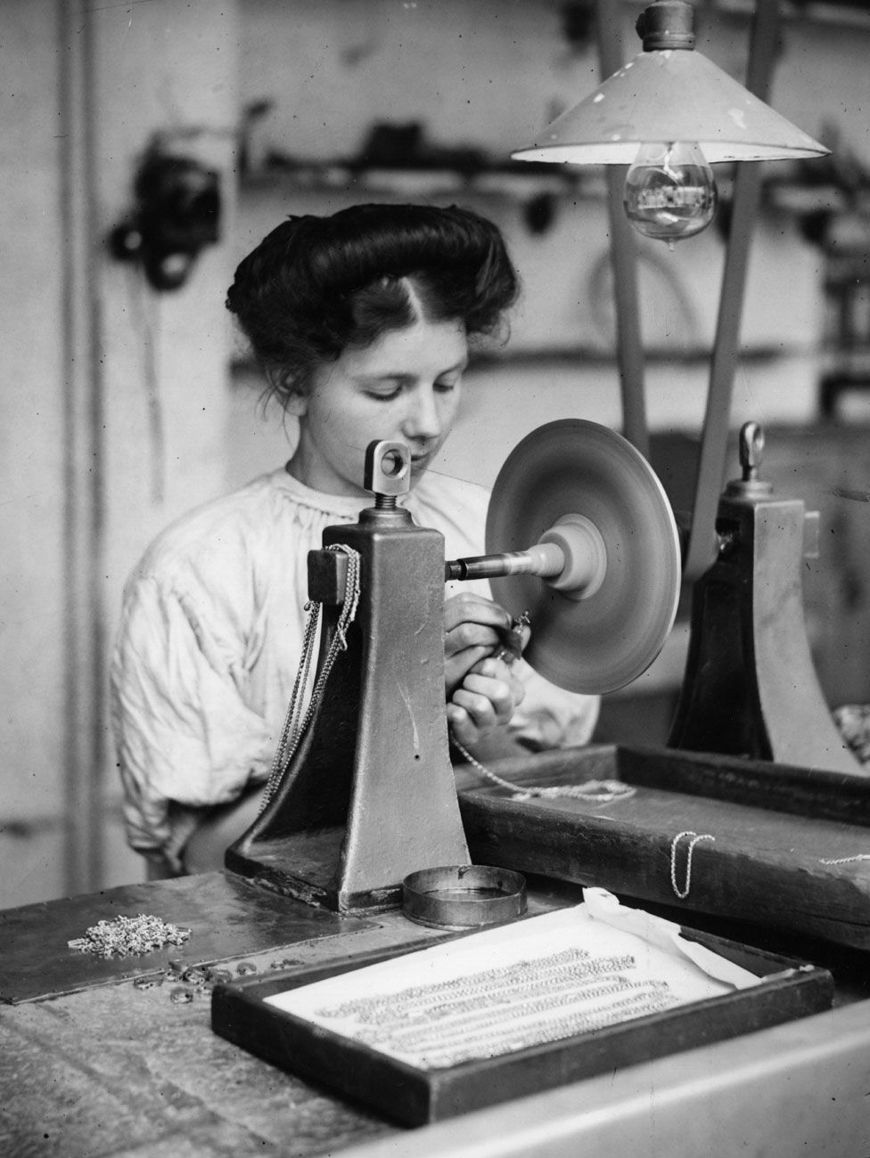 A factory girl works on the finishing of a length of gold chain in 1909