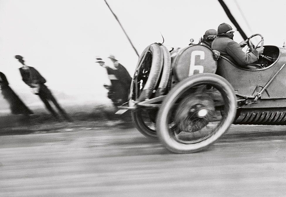 A racing car zooms past spectators