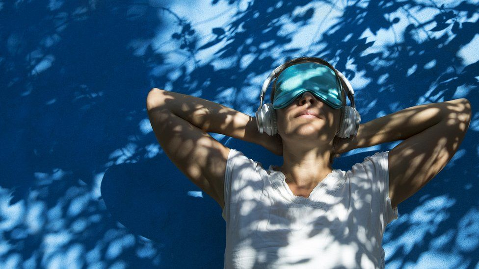 woman in eye shade listening to music