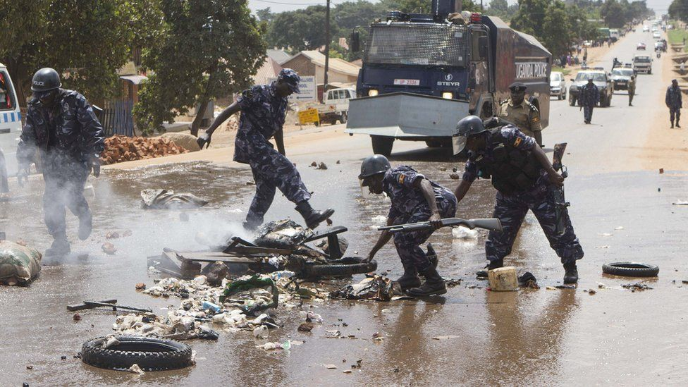 Uganda police officers remove barricades set by people demonstrating on a road in Kasangati on July 9, 2015, after presidential hopefuls former Prime Minister Amama Mbabazi and opposition leader Kizza Besigye were arrested by the Ugandan police.