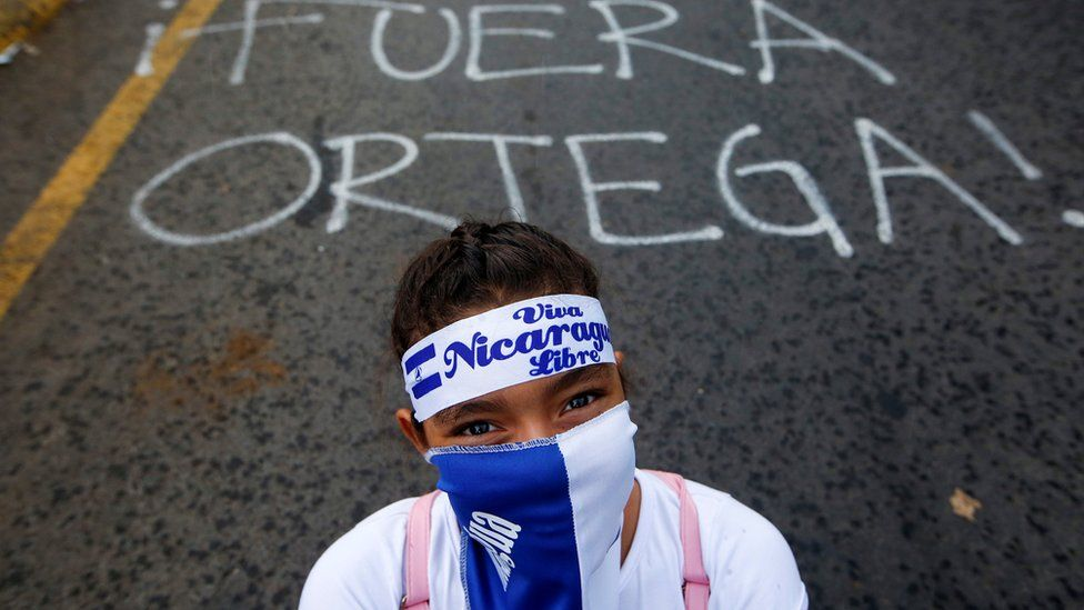 """A demonstrator stands next to a graffiti that reads """"Ortega Out"""" during a protest march against Nicaraguan President Daniel Ortega's government in Managua, Nicaragua May 26, 2018"""