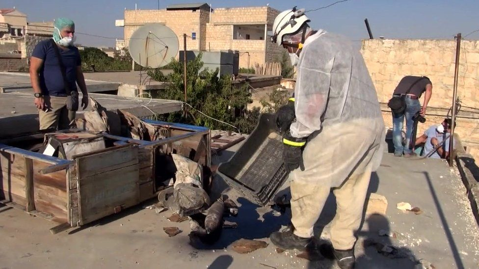 Workers collect samples from the site of an alleged chemical weapons attack in Syria