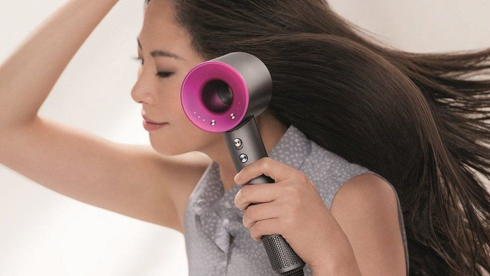 A woman using Dyson hairdryer