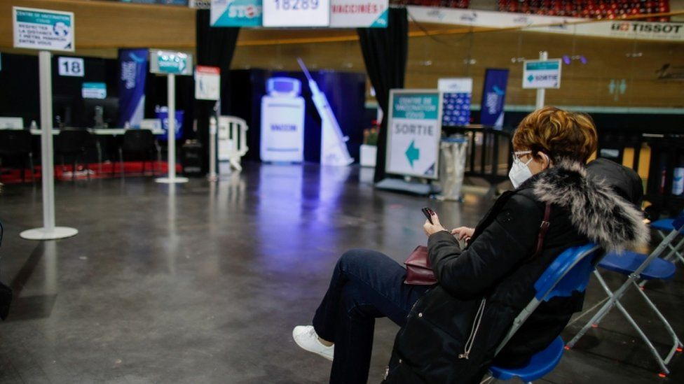 A woman waits to be vaccinated at the indoor Velodrome National of Saint-Quentin-en-Yvelines in Montigny-le-Bretonneux, southwest of Paris