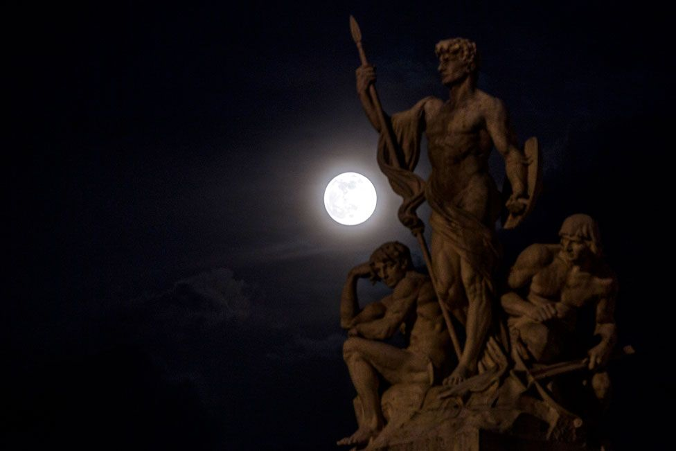 The pink supermoon rises through the clouds behind a statue of the Vittoriano in Rome, Italy