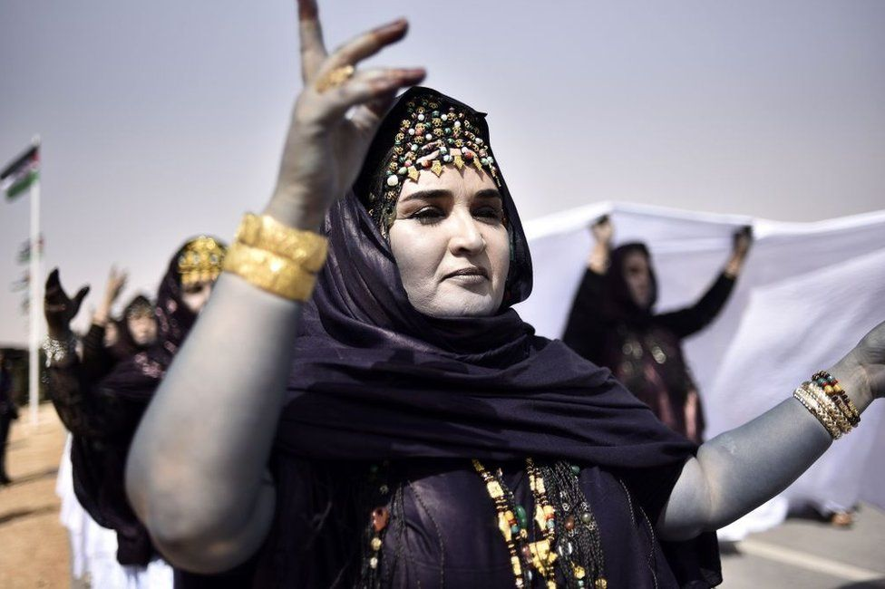 Sahrawi women perform a dance in the parade. Their faces are painted white.