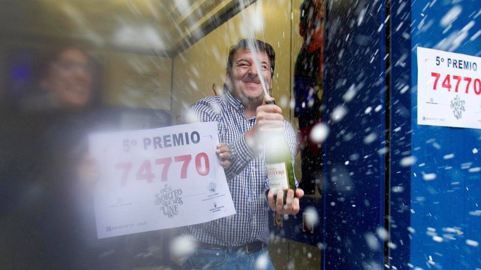 """People celebrate selling the number 74770, winner of one of the eight 5th prizes of """"El Gordo""""."""