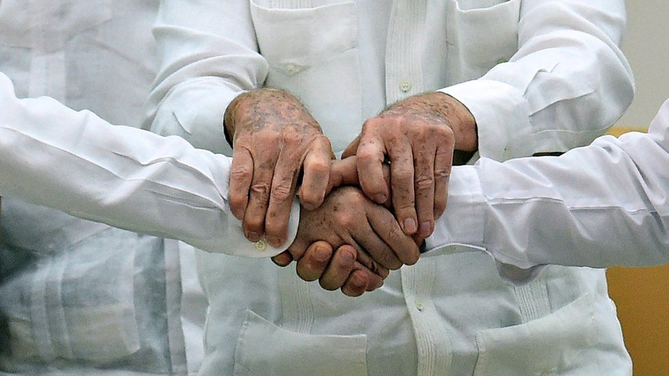 A close-up of the hands of Juan Manuel Santos (left), Raul Castro (centre) and Timochenko (right)