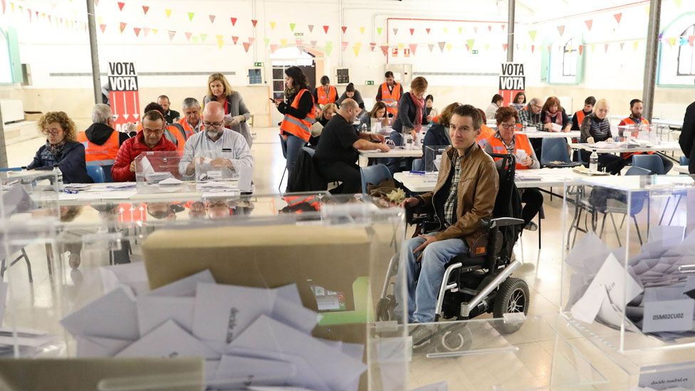 Mr Soto is seen sitting in his wheelchair in the middle of a busy polling station, with ballot boxes stacked neatly filled with papers in the foreground. He appears to be casting his vote